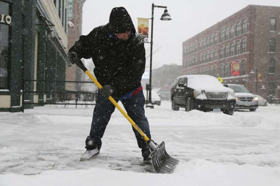 Bernardo Robles, employee of Pints Pub N Patio shovels snow off the sidewalk outside of the business on Monday, Jan. 5, 2015, in downtown Des Moines, Iowa. Meteorologist Kurt Kotenberg says the heaviest snowfall in Iowa is expected Monday afternoon and evening, which may affect commuters leaving work. (AP Photo/The Des Moines Register, Kelsey Kremer)