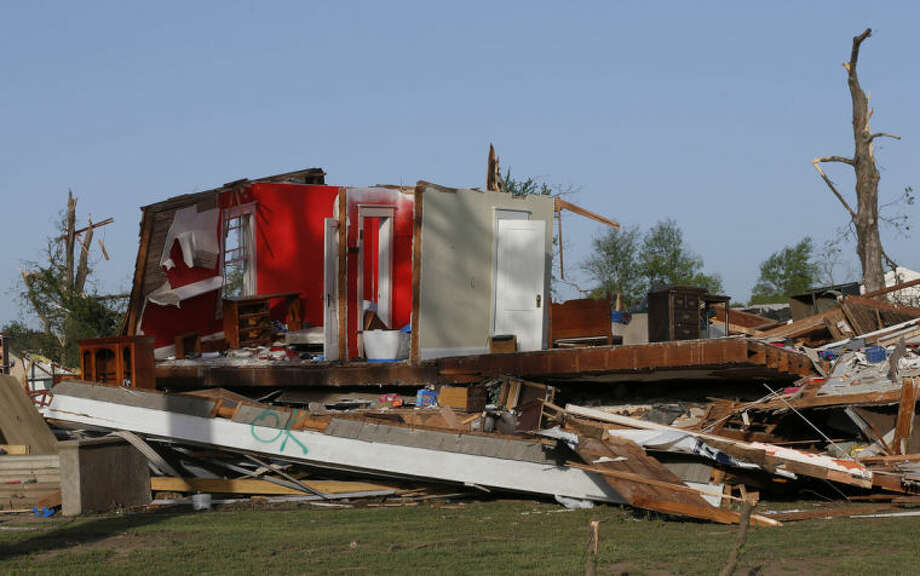 The remains of a home damaged by a tornado Sunday evening stands in Baxter Springs, Kan., Monday, April 28, 2014. The tornado left a trail of shattered homes, twisted metal and hanging power lines. One person died, but it was not clear whether the death was related to the storm. Volunteers were meeting early Monday to discuss cleanup efforts. Emergency officials say 60 to 70 homes and 20 to 25 businesses were destroyed or damaged in the town. (AP Photo/Orlin Wagner)