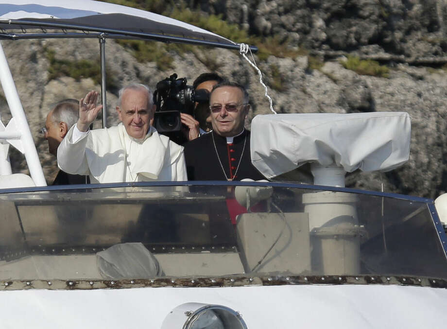 FILE -- In this file photo taken aboard an Italian Coast Guard boat at the island of Lampedusa, southern Italy, on July 8, 2013, Pope Francis is flanked by Monsignor Francesco Montenegro as he waves to faithful. Francesco Montenegro, a Sicilian, was at his side when Francis made his first trip a few months into his papacy. Montenego welcomed the pontiff to Lampedusa, a tiny Sicilian island whose people have helped thousands of migrants stranded by smugglers offshore. The pontiff has repeatedly denounced human trafficking and urged more attention to people on the margins of society. He also has thundered against Mafiosi in other voyages to Italy's south, and Montenegro's Agrigento diocese includes towns where people have dared rebel against Cosa Nostra's evil dominance. Pope Francis named 15 new cardinals Sunday, including Francesco Montenegro, selecting them from 14 nations, including far-flung corners of the world such as Tonga, New Zealand, Cape Verde and Myanmar, to reflect the diversity of the church and its growth in places like Asia and Africa compared to affluent regions. (AP Photo/Gregorio Borgia)