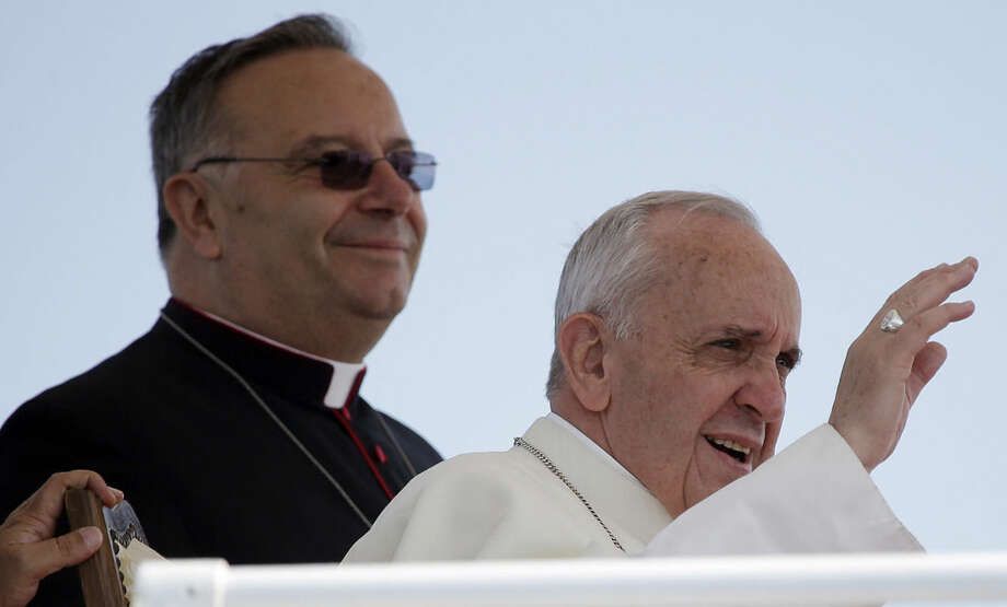 FILE -- In this file photo taken aboard an Italian Coast Guard boat at the island of Lampedusa, southern Italy, on July 8, 2013, Pope Francis is flanked by Monsignor Francesco Montenegro as he waves to faithful. Francesco Montenegro, a Sicilian, was at his side when Francis made his first trip a few months into his papacy. Montenego welcomed the pontiff to Lampedusa, a tiny Sicilian island whose people have helped thousands of migrants stranded by smugglers offshore. The pontiff has repeatedly denounced human trafficking and urged more attention to people on the margins of society. He also has thundered against Mafiosi in other voyages to Italy's south, and Montenegro's Agrigento diocese includes towns where people have dared rebel against Cosa Nostra's evil dominance. Pope Francis named 15 new cardinals Sunday, selecting them from 14 nations, including far-flung corners of the world such as Tonga, New Zealand, Cape Verde and Myanmar, to reflect the diversity of the church and its growth in places like Asia and Africa compared to affluent regions. (AP Photo/Gregorio Borgia)