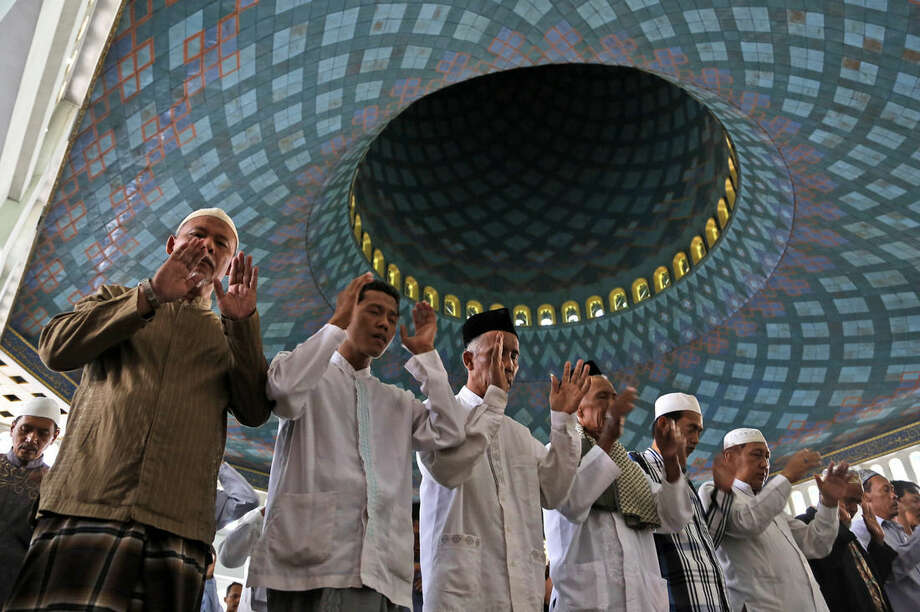 Indonesian Muslim men pray during a special prayer for the victims of AirAsia Flight 8501 at Al Akbar Mosque in Surabaya, East Java, Indonesia, Friday, Jan. 2, 2015. More ships arrived Friday with sensitive equipment to hunt for the fuselage of the flight and the more than 145 people still missing since it crashed into the sea five days ago. (AP Photo/Dita Alangkara)