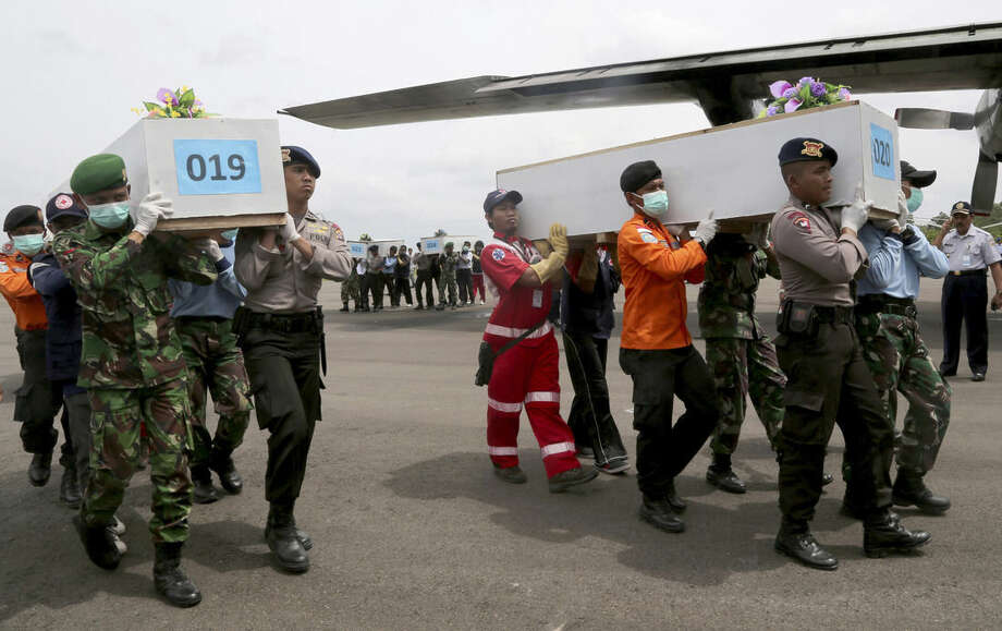 Members of the National Search and Rescue Agency carry coffins containing bodies of the victims aboard AirAsia Flight 8501 to transfer to Surabaya at the airport in Pangkalan Bun, Indonesia, Saturday, Jan. 3, 2015. Indonesian officials were hopeful Saturday they were honing in on the wreckage of the flight after sonar equipment detected two large objects on the ocean floor, a full week after the plane went down in stormy weather. (AP Photo/Tatan Syuflana)