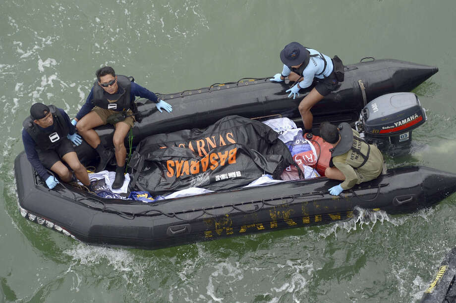 Indonesian Navy personnel carry a plastic bag containing the dead body of a passenger of AirAsia Flight 8501 at sea off the coast of Pangkalan Bun, Indonesia, Saturday, Jan. 3, 2015. Indonesian officials were hopeful Saturday they were honing in on the wreckage of the flight after sonar equipment detected two large objects on the ocean floor, a full week after the plane went down in stormy weather. (AP Photo/Adek Berry, Pool)