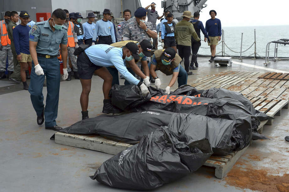 Indonesian Navy personnel lay plastic bags containing the bodies of victims of AirAsia Flight 8501 found at sea off the coast of Pangkalan Bun, Indonesia, Saturday, Jan. 3, 2015. Indonesian officials were hopeful Saturday they were honing in on the wreckage of the flight after sonar equipment detected two large objects on the ocean floor, a full week after the plane went down in stormy weather. (AP Photo/Adek Berry, Pool)