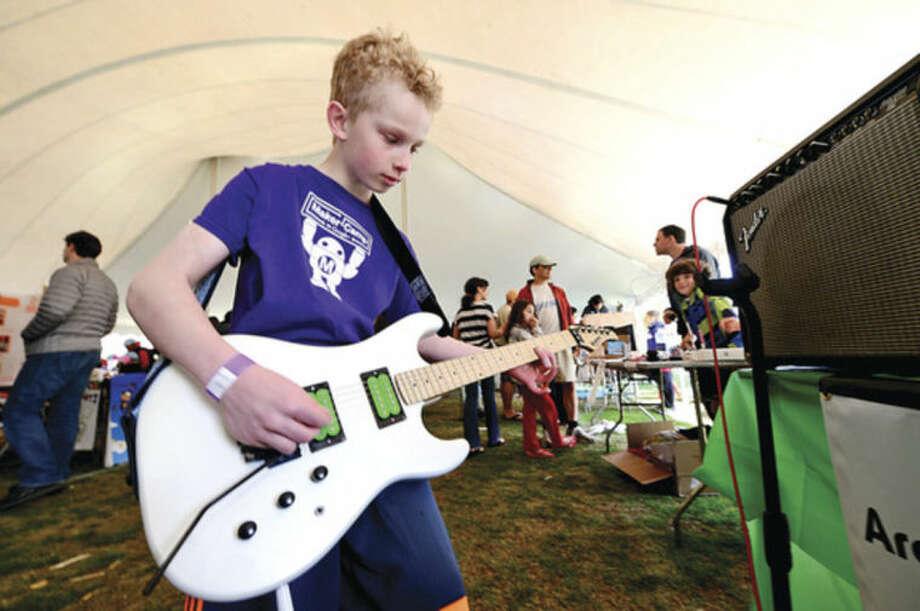 Hour photo / Erik Trautmann Luke Lileika plays guitar through a Rullywear effecs box at the annual Mini Makers Faire at the Jessup Green in Westport Saturday.