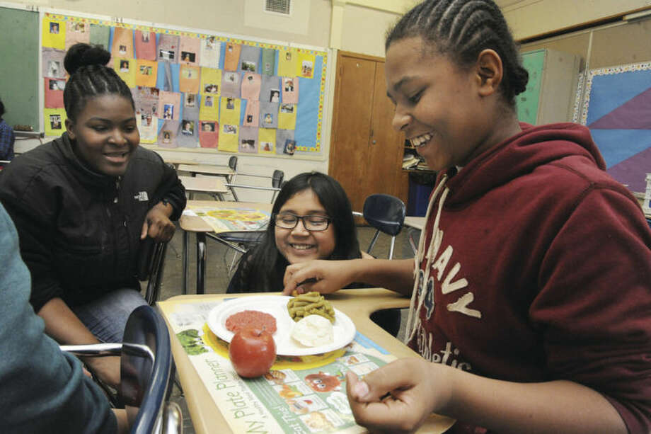 Hour photo / Matthew VinciShelly Decolline, Joceyln Gonzalez and Brenda Diaz learn about healthy eating at the Kids' Fan program at Nathan Hale Middle School.