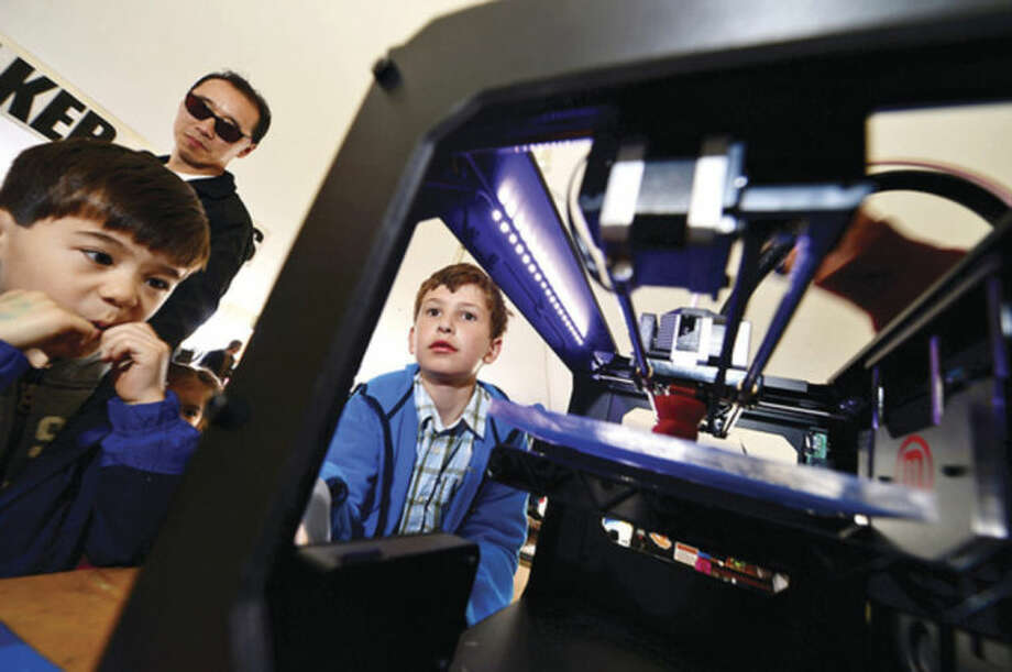 Hour photos / Erik TrautmannAbove, Connor Yuan, 5, and Jeffrey Pogue, 9, check out a Maker Bot 3D printer during the annual Mini Maker Faire at the Jessup Green in Westport. Below, Leslie Flinn and her son Grady check out Quadframe UAVs at the annual Mini Maker Faire.