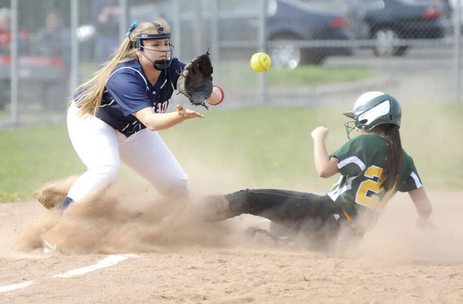 Hour photo/John NashBrien McMahon third baseman Mackenzie Stamp, left, waits for the ball to arrive as Trinity Catholic's Alexis Melfi slides safely into third base during Friday's FCIAC softball game in Norwalk. The host Senators eked out a 1-0 win.