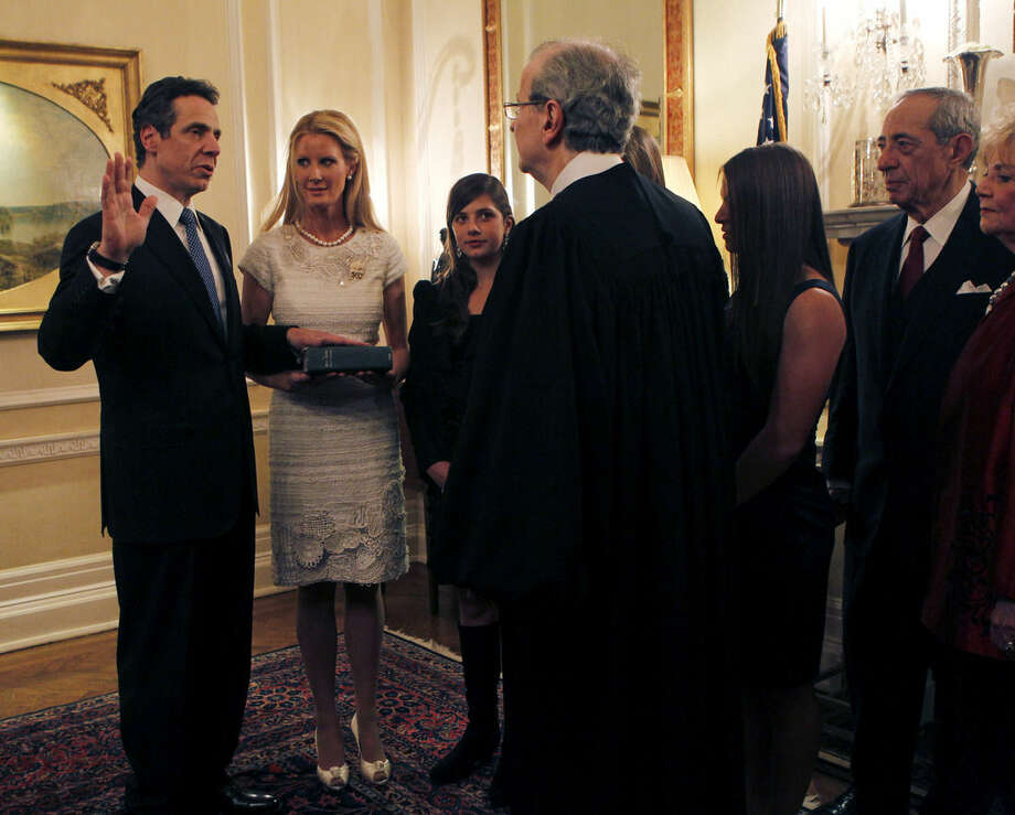 FILE - In this Dec. 31, 2010, file photo, New York Gov. Andrew Cuomo, is sworn in by Chief Judge Jonathan Lippman as Cuomo's girlfriend, Sandra Lee, holds a Bible, during a private ceremony at the Executive Mansion in Albany, N.Y. Cuomo's father and former New York Gov. Mario Cuomo stands at right. Mario Cuomo died Thursday, Jan. 1, 2015, the day his son Andrew started his second term as governor, the New York governor's office confirmed. He was 82. (AP Photo/Mike Groll, File)
