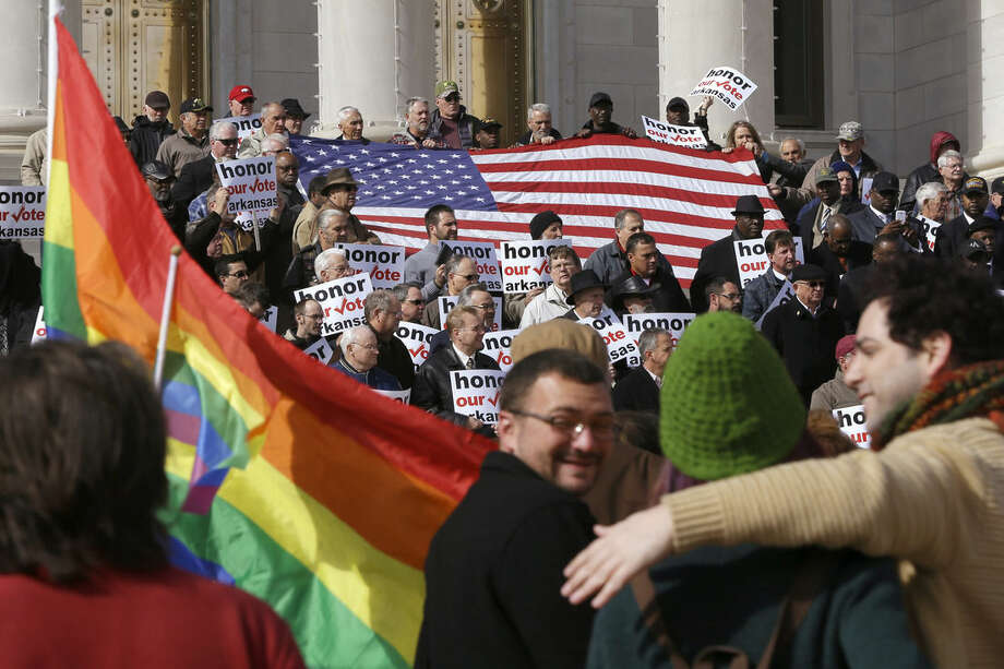 FILE - In a Wednesday, Nov. 19, 2014 file photo, supporters of Arkansas' law banning same sex marriage, top, hold a rally at the Arkansas state Capitol in Little Rock, Ark., as protestors carry flags and shout. An gay rights ordinance passed in August by the city council in Fayetteville, Ark., was repealed by voters on Dec. 10. Even as same-sex marriage edges closer to becoming legal nationwide, gay-rights advocates face other challenges in 2015 that may not bring quick victories. (AP Photo/Danny Johnston, File)