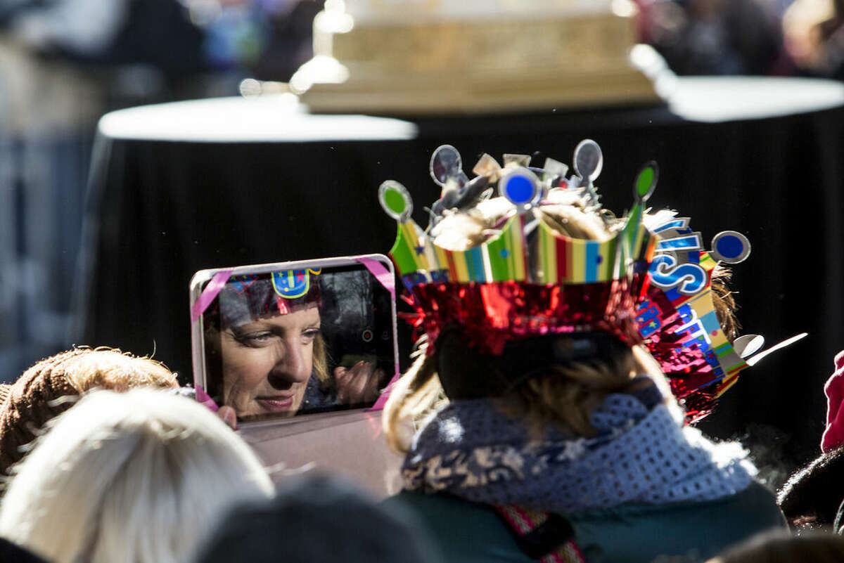 An Elvis fan, wearing a birthday hat, takes pictures with her tablet during the 80th birthday celebration for Elvis Presley at Graceland, Thursday, Jan. 8, 2015, in Memphis, Tenn. A large crowd gathered for the celebration even though the temperature was below 20 degrees. (AP Photo/The Commercial Appeal, Brad Vest)