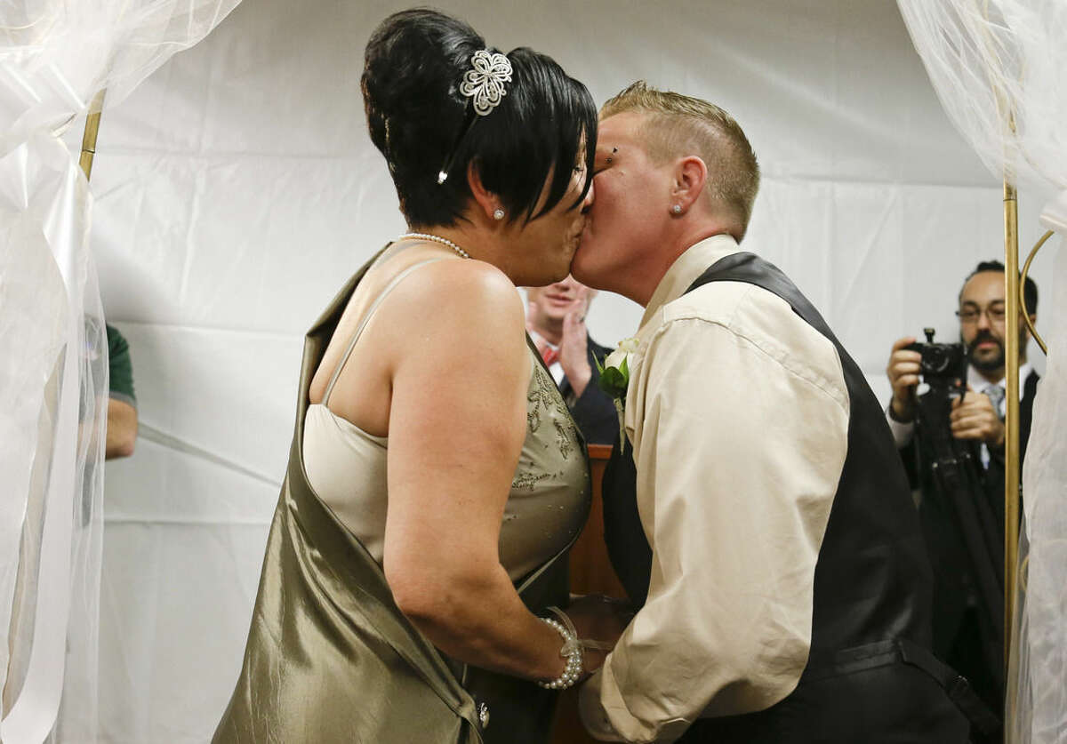 Tracy Benjamin, left, and Tarina Golly kiss after they were married at the Osceola County Court, early Tuesday, Jan. 6, 2015, in Kissimmee, Fla. Florida's ban on same-sex marriage ended statewide at the stroke of midnight Monday, and court clerks in some Florida counties wasted no time, issuing marriage licenses and performing weddings for same-sex couples overnight. (AP Photo/John Raoux)