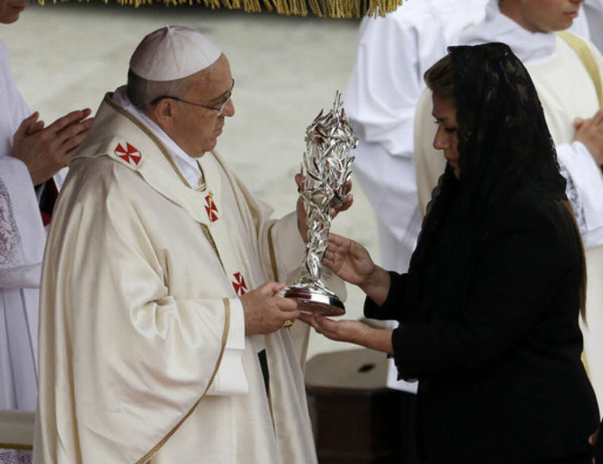 Pope Francis receives the relic of Pope John Paul II from Floribeth Mora, a Costa Rican woman whose inoperable brain aneurysm purportedly disappeared after she prayed to John Paul II, during a solemn ceremony in St. Peter's Square at the Vatican, Sunday, April 27, 2014. Pope Francis has declared his two predecessors John XXIII and John Paul II saints in an unprecedented canonization ceremony made even more historic by the presence of retired Pope Benedict XVI. (AP Photo/Gregorio Borgia)
