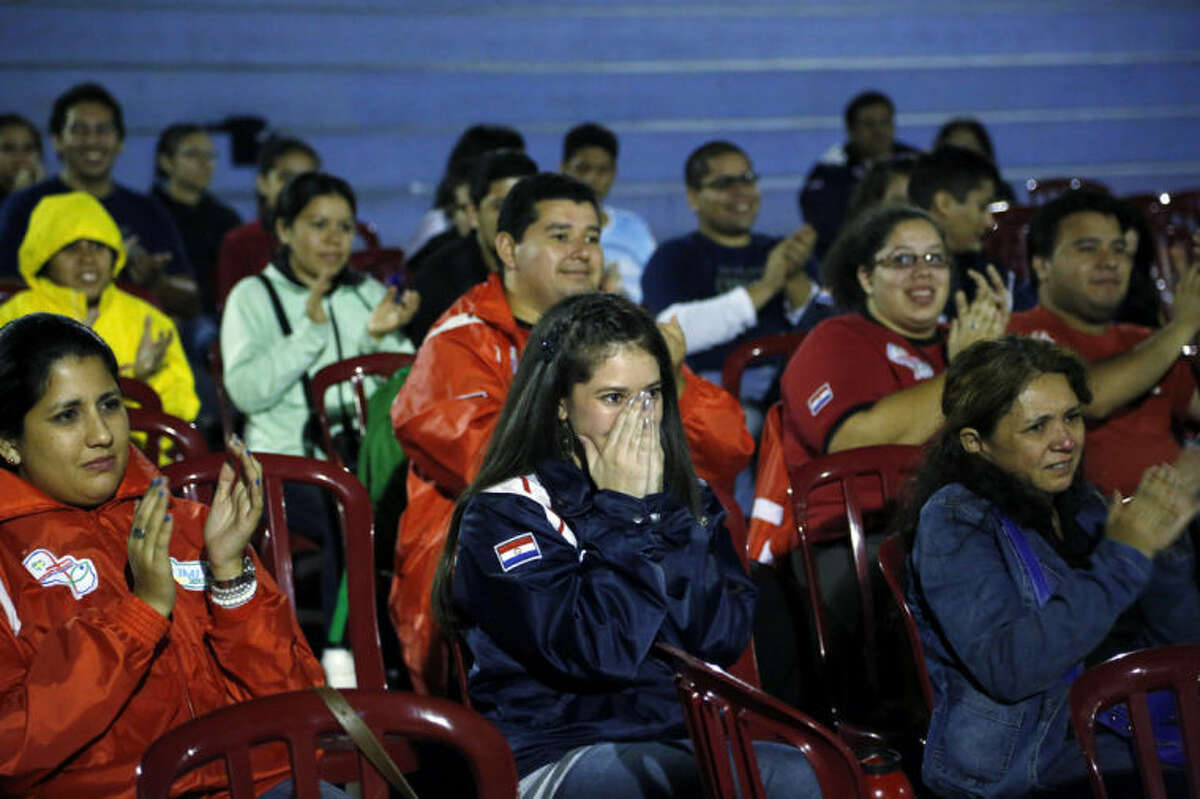 Paraguay's people react as they look at a TV screen showing the Vatican ceremony for a historic day of four popes, with Popes Francis and Benedict XVI honoring John XXIII and John Paul II by declaring them saints, at Nazareth church in Asuncion, Paraguay, Sunday, April 27, 2014. (AP Photo/Jorge Saenz)