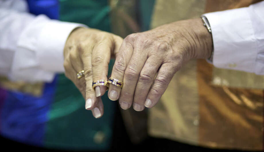 John and Shel Goldstein display their wedding rings before a group wedding, Tuesday, Jan. 6, 2015, in Delray Beach, Fla. Florida's ban on same-sex marriage ended statewide at the stroke of midnight Monday, and court clerks in some Florida counties wasted no time, issuing marriage licenses overnight to same-sex couples. But they still were beaten to the punch by a Miami judge who found no need to wait until the statewide ban expired. (AP Photo/J Pat Carter)