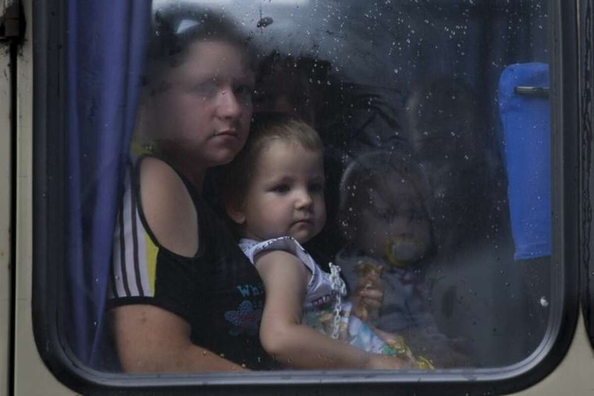 Children and their mother look through a bus window while leaving the city fearing shelling attacks during a fighting between Ukrainian government forces and pro-Russian militants in Slovyansk, Ukraine, Thursday, May 29, 2014. In Slovyansk, a city 90 kilometers (55 miles) north of Donetsk which that has seen constant clashes over the past few weeks, residential areas came under mortar shelling Wednesday from government forces. (AP Photo/Alexander Zemlianichenko)