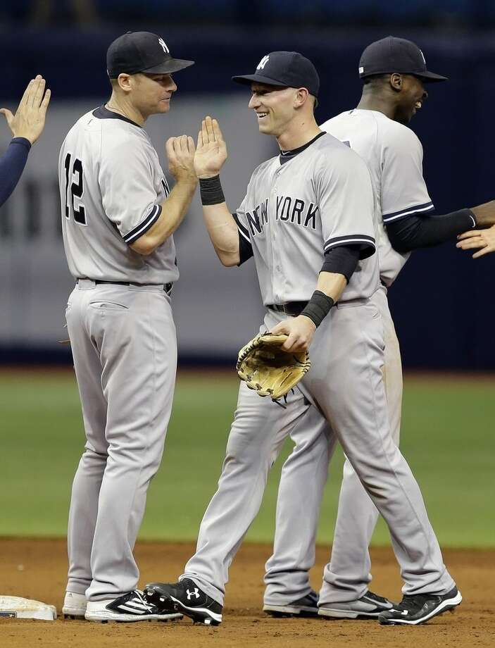New York Yankees' Slade Heathcott, center, celebrates with teammates, including Chase Headley, left, and Didi Gregorius, right, after the Yankees defeated the Tampa Bay Rays 4-1 during a baseball game Monday, Sept. 14, 2015, in St. Petersburg, Fla. Heathcott had a three-run home run in the win. (AP Photo/Chris O'Meara)