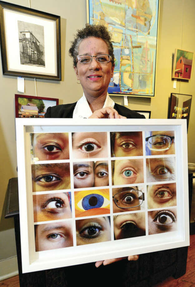"Hour photo / Erik TrautmannNorwalk Historical Society Executive Director Diane Jellerette displays some of the winners of the ""Diversecity"" photo contest which will be exhibited starting Thursday May 22."