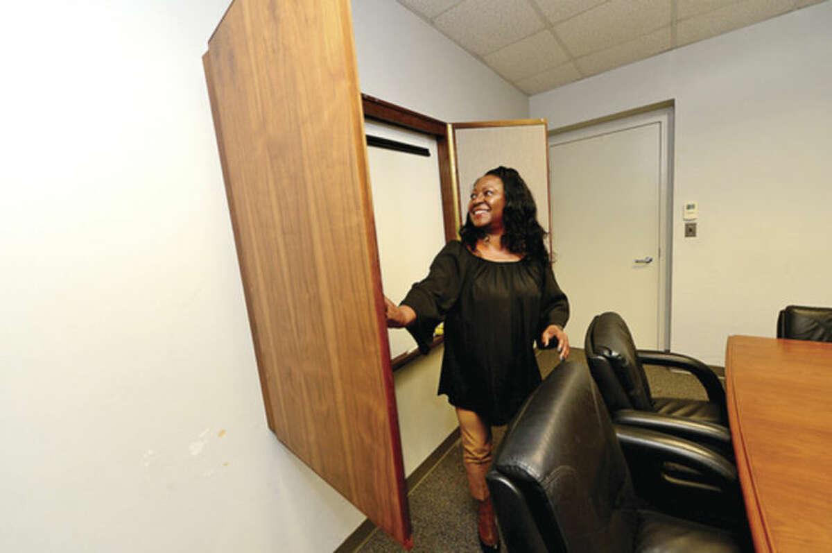 Hour photo / Erik Trautmann Sally Johnson, executive assistant to the Mayor of Norwalk, shows off the furniture that Northrop Grumman donated to the city from their former Norwalk facility.