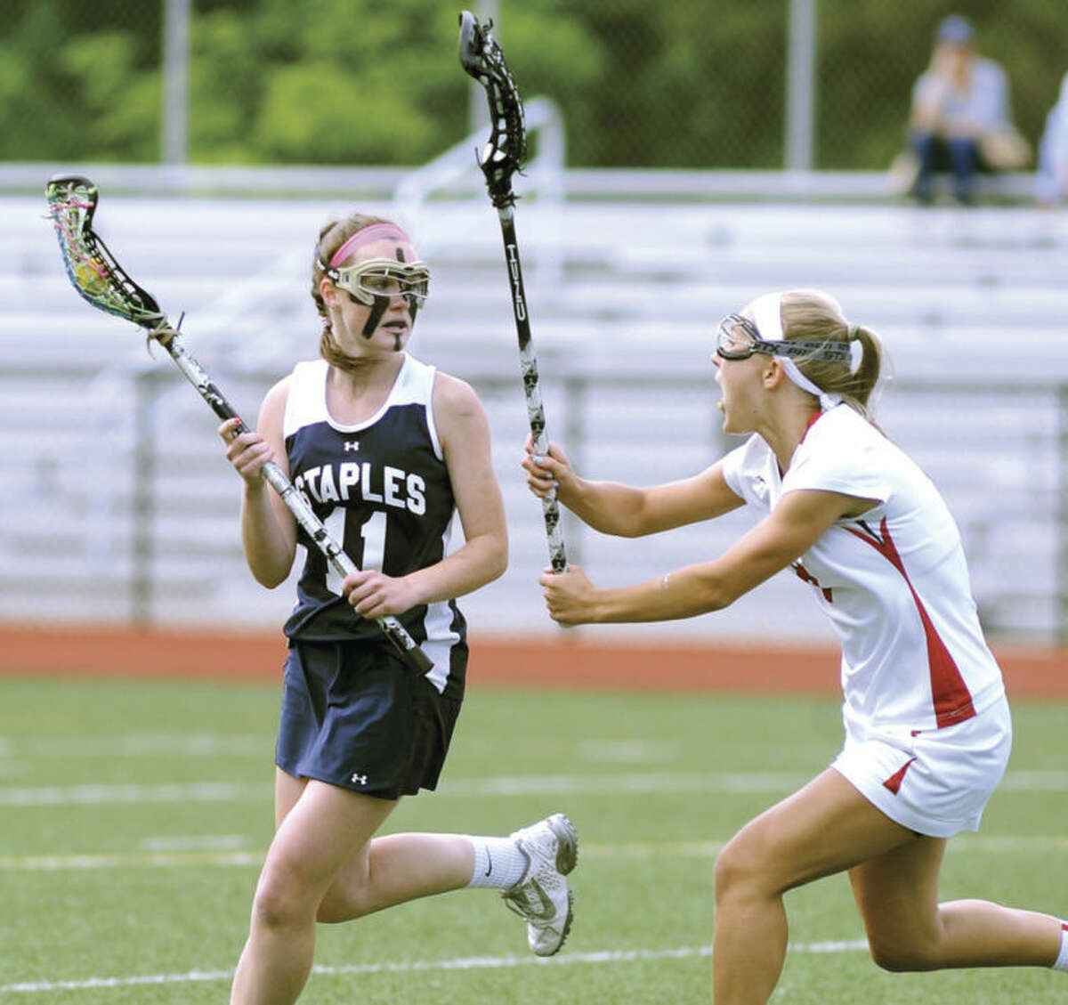 Hour photo/John Nash Staples' Colleen Bannon protects the ball from Greenwich defender Emily Ludington during Friday's FCIAC girls lacrosse quarterfinal at Cardinal Stadium in Greenwich.
