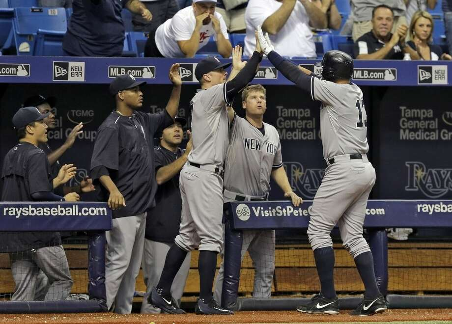 New York Yankees' Alex Rodriguez, right, gets high fives from teammates after being taken out of the game against the Tampa Bay Rays during the ninth inning of a baseball game Monday, Sept. 14, 2015, in St. Petersburg, Fla. Rodriguez had an RBI double in the inning. (AP Photo/Chris O'Meara)