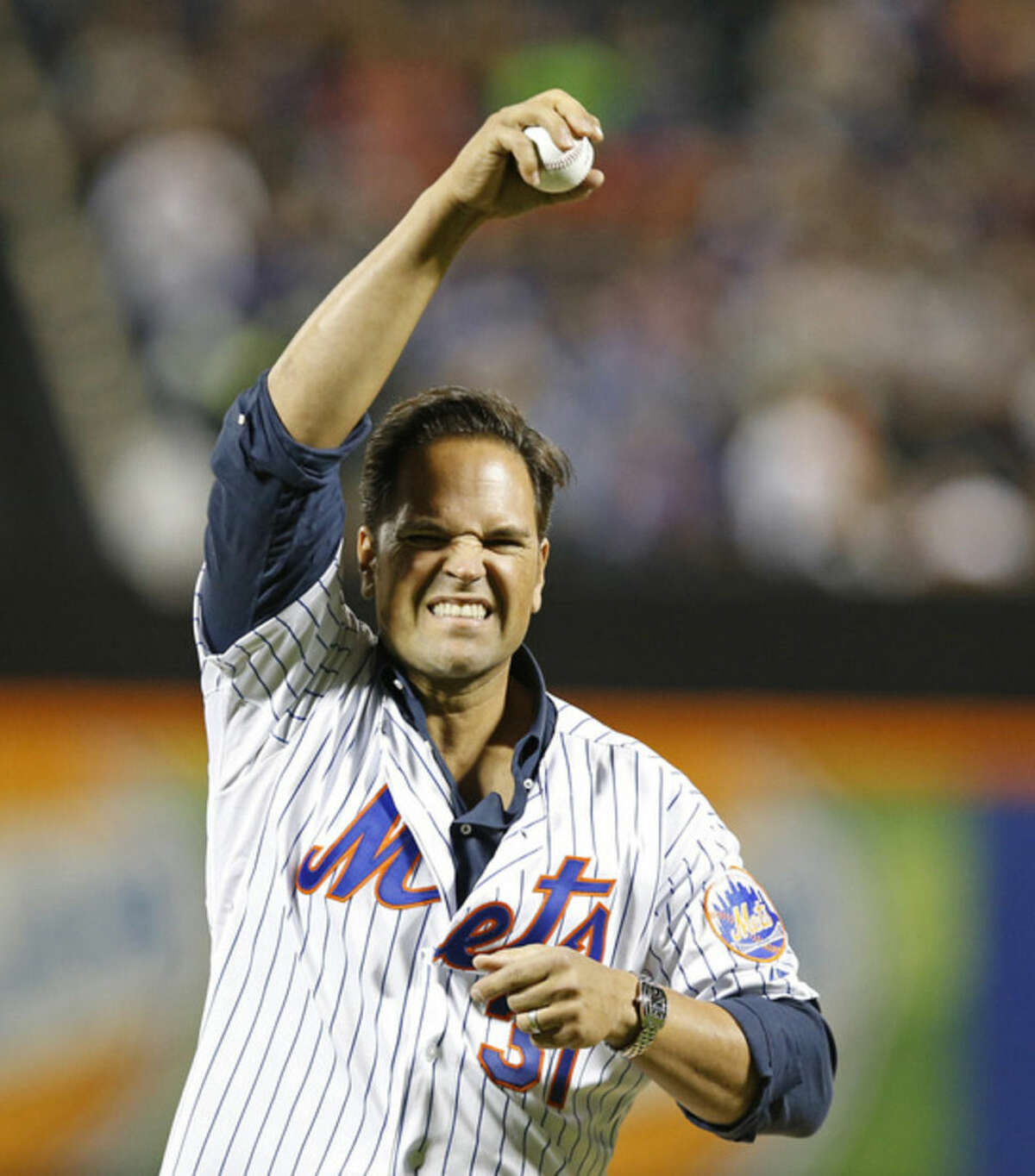 Former New York Mets catcher Mike Piazza grimaces as he warms up his arm before throwing out the ceremonial first pitch before a baseball game between the New York Mets and the New York Yankees in New York, Sunday, Sept. 20, 2015. (AP Photo/Kathy Willens)