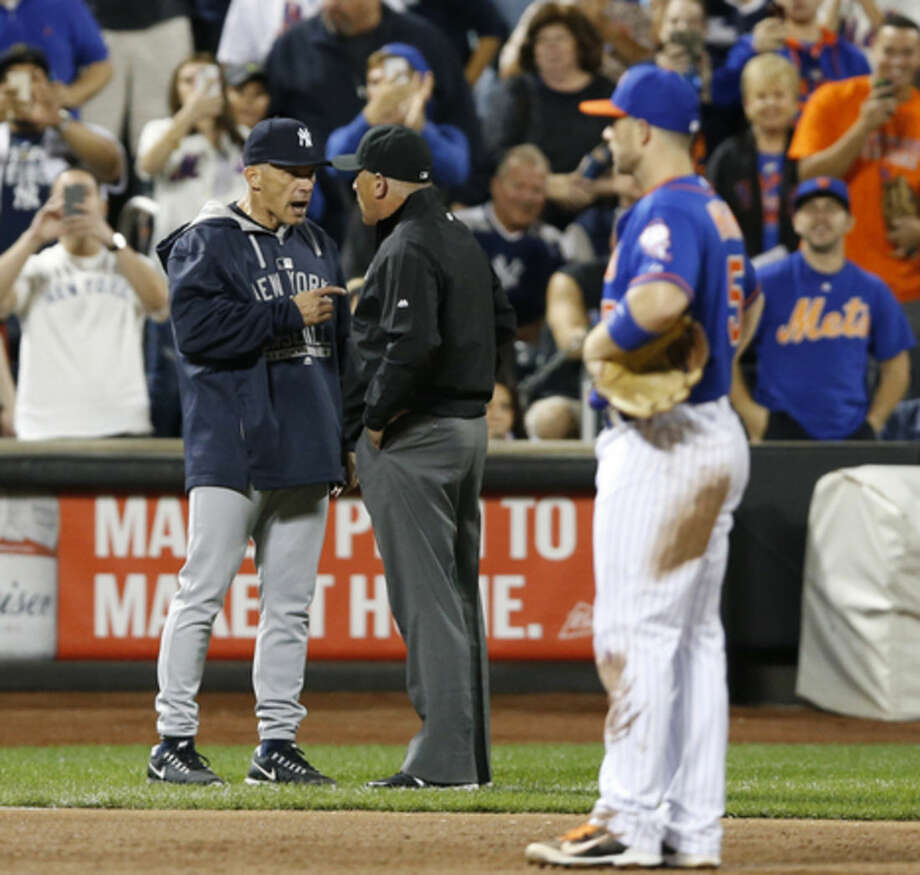 New York Yankees manager Joe Girardi, left, argues with third base umpire John Hirschbeck as New York Mets third baseman David Wright (5) watches and fans snap cell phone photos during the second inning of a baseball game in New York, Sunday, Sept. 20, 2015. (AP Photo/Kathy Willens)