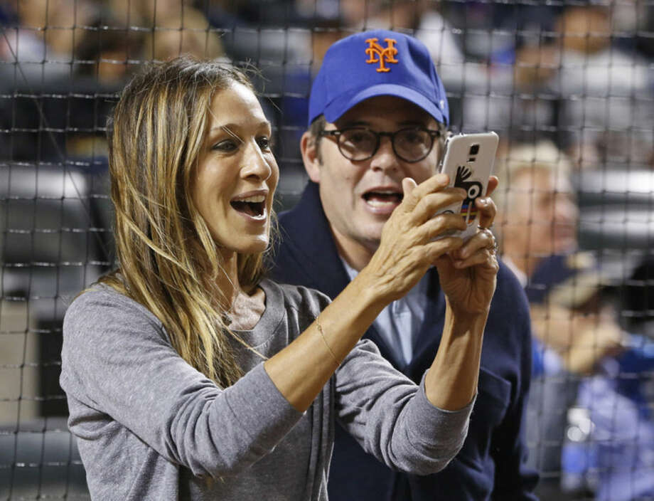 Actress Sarah Jessica Parker, snaps a cell phone photo with her husband, Broadway actor Matthew Broderick on the field before a baseball game between the New York Mets and the New York Yankees in New York, Sunday, Sept. 20, 2015. (AP Photo/Kathy Willens)