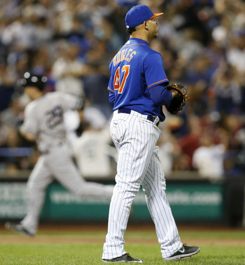 New York Yankees Dustin Ackley, left, trots the bases after hitting a sixth-inning, three-run home run as New York Mets relief pitcher Hansel Robles turns toward the outfield in a baseball game in New York, Sunday, Sept. 20, 2015. (AP Photo/Kathy Willens)