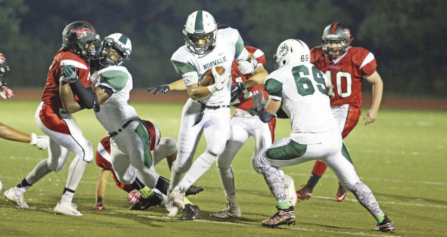 Hour photo/Danielle CallowayAbove, Norwalk High School's Brendan Brown, center, makes a play between his teammates' blocks during an away game against Fairfield Warde Friday evening. Norwalk opened the season with a win. Below, Brien McMahon's Marvin Jean-Pierre had four sacks in his team's win over Wilton.