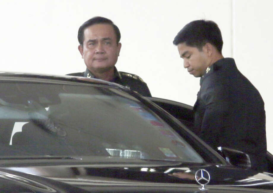Thai Army Chief Gen. Prayuth Chan-ocha, left, gets in a car as he leaves the Army Club shortly before staging the coup in Bangkok, Thailand Thursday, May 22, 2014. Thailand's army chief announced a military takeover of the government Thursday, saying the coup was necessary to restore stability and order after six months of political deadlock and turmoil. (AP Photo/Apichart Weerawong)
