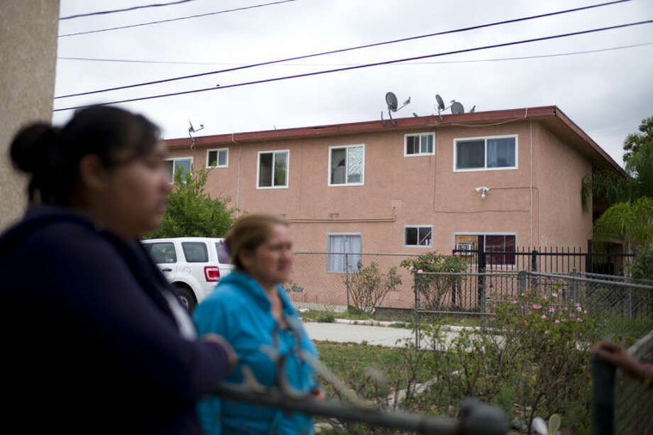 A group of women from the neighborhood chat near an apartment building where suspect Isidro Garcia lived on Thursday, May 22, 2014, in Bell Gardens, Calif. A woman who disappeared a decade ago as a 15-year-old reunited recently with her mother, who convinced her to go to authorities to report that she had been kidnapped and raped by Garcia who is now her husband and father of her daughter. (AP Photo/Jae C. Hong)