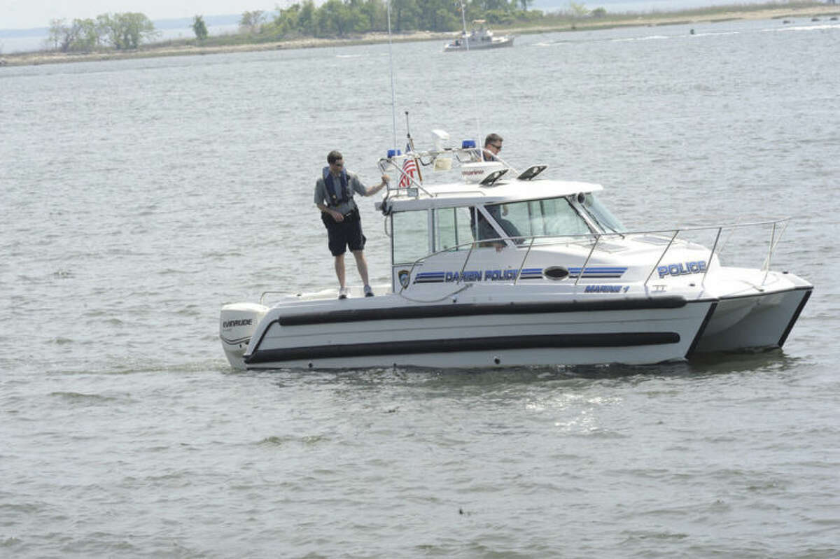 Darien police one of many in the search for a member of a turned over boat missing off the shore at Calf Pasture Beach in Norwalk. Hour photo/Matthew Vinci