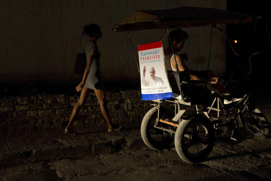 A poster featuring Pope Francis and a welcome message decorates the back of a tricycle taxi in Havana, Cuba, Friday, Sept. 18, 2015. Francis will visit Cuba from Sept. 19-22, before arriving in the United States, making him the third pontiff to visit the island nation. (AP Photo/Alessandra Tarantino)