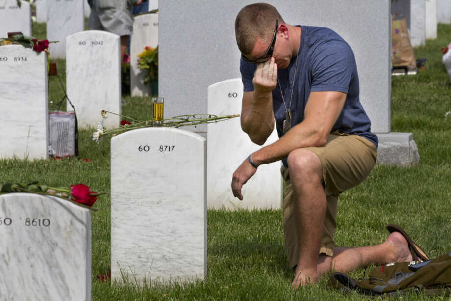 Former Army Sgt. Anthony Brown, 31, of Arlington, Va., wipes away tears as he visits his best friend, Army Sgt. Scott Kirkpatrick, on Memorial Day at Arlington National Cemetery in Arlington, Va., Monday, May 26, 2014. Kirkpatrick died serving in Iraq in 2007 at the age of 27, and is buried in Section 60, where many of the soldiers who died in Iraq and Afghanistan are buried, (AP Photo/Jacquelyn Martin)