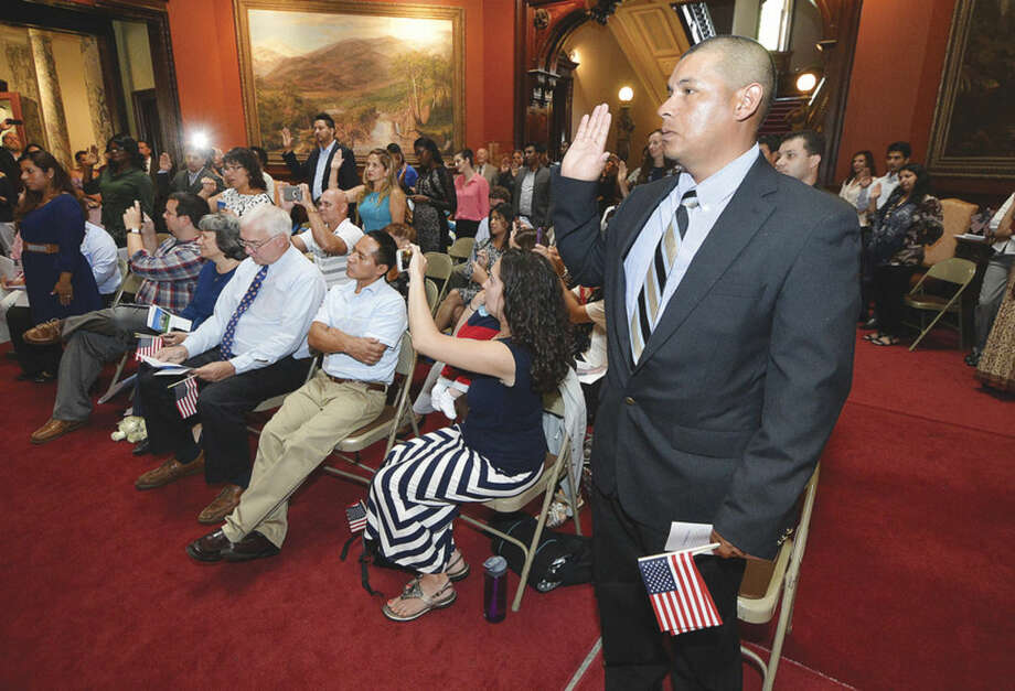 Hour Photo/Alex von Kleydorff Javier Chirinos from Honduras takes the Oath of Allegiance with about two dozen more people to become a U.S. citizen during a special Naturalization ceremony held at Norwalk's Lockwood Matthews Mansion Museum on Tuesday