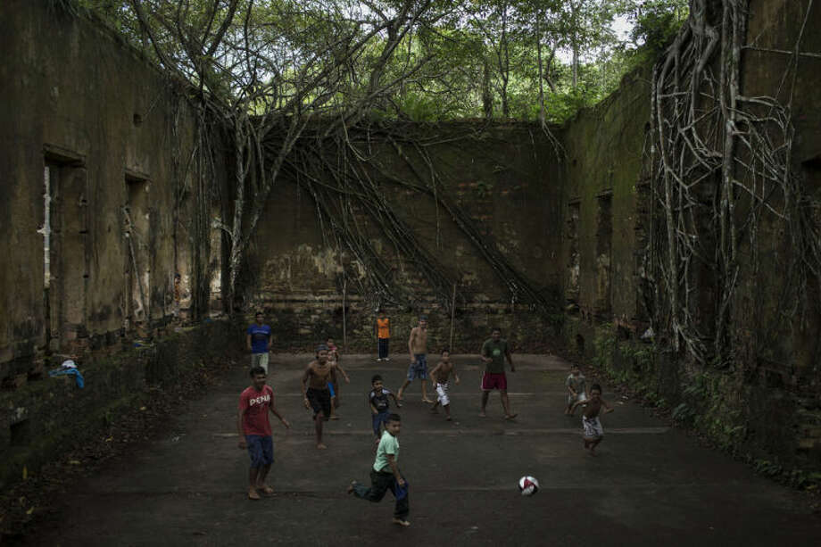 In this May 21, 2014, photo, Children and adults play soccer in the ruins of Paricatuba, near Manaus, Brazil. Manaus is one of the host cities for the 2014 World Cup in Brazil. (AP Photo/Felipe Dana, File)