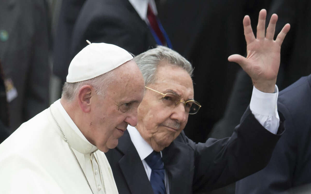 In this Saturday, Sept. 19, 2015 photo, Cuba's President Raul Castro waves as he escorts Pope Francis at the airport in Havana, Cuba. Pope Francis began his 10-day trip to Cuba and the United States, embarking on his first trip to the onetime Cold War foes after helping to nudge forward their historic rapprochement. (AP Photo/Ramon Espinosa)