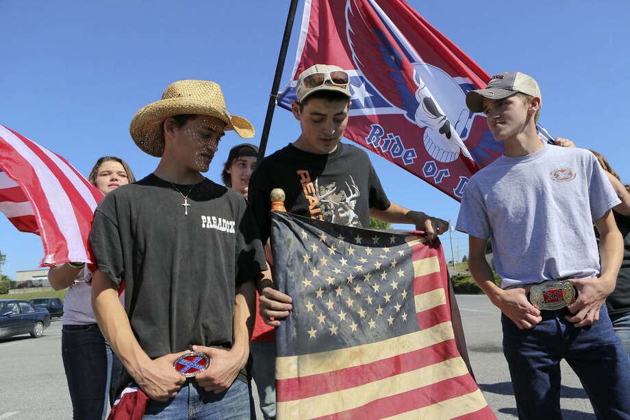 Christiansburg High School students bearing American and Confederate flags gather in a shopping center parking lot after being suspended from school property in Christiansburg, Va. Thursday, Sept. 17, 2015. Roughly 20 students at the Virginia high school received a one-day suspension for wearing clothing displaying the Confederate flag. A rally was also organized outside the school Thursday to protest a new school policy banning vehicles with Confederate symbols from its parking lot. (Matt Gentry /The Roanoke Times via AP) LOCAL TELEVISION OUT; SALEM TIMES REGISTER OUT; FINCASTLE HERALD OUT; CHRISTIANBURG NEWS MESSENGER OUT; RADFORD NEWS JOURNAL OUT; ROANOKE STAR SENTINEL OUT; MANDATORY CREDIT