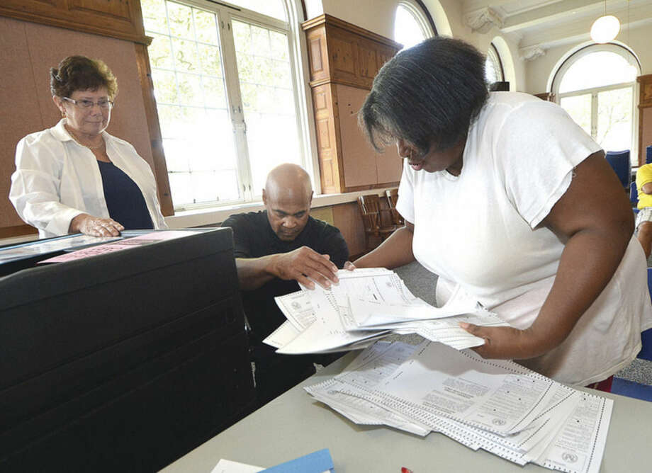 Hour Photo/Alex von Kleydorff Ronald Banks hands ballots to Arissa Scovens during a recount of the tally at City Hall for Democratic primaries District A Common Council and Board of Ed and 2nd taxing district