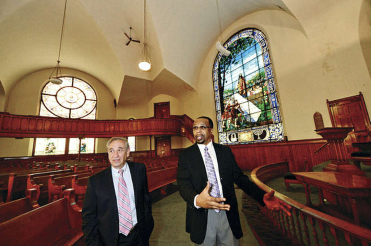 Hour photo / Erik Trautmann Macedonia Church's Rev. DeWitt Stevens thanks attorney Steven Grushkin as they take a tour of former First United Methodist Church on West Ave Friday which Macedonia Church recently bought and intend to rennovate.