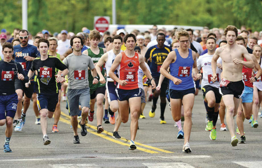 Hour photo/Erik TrautmannRunners take off from the starting line during the 21st annual Weston Memorial Day 5K road race Saturday morning.