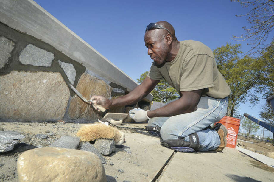 Hour Photo/Alex von Kleydorff Mason Bobby Orr with Terry Contracting works on the stone veneer sea wall using repourposed stones from the former wall at Calf Pasture Beach