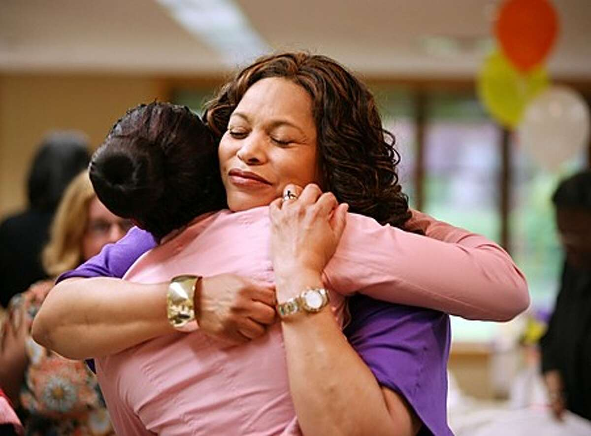 Minister Robin Dancey hugs Lashay McQueen during Macedonia Women''s Ministry''s