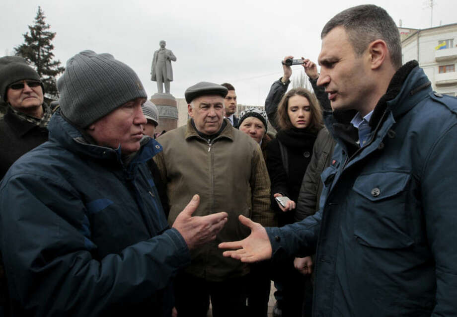 Ukrainian lawmaker and chairman of the Ukrainian party Udar (Punch), former WBC heavyweight boxing champion Vitali Klitschko, right, speaks with locals in Donetsk, Ukraine, Sunday, March 9, 2014. At background left is a statue of Soviet revolutionary leader Vladimir Lenin. (AP Photo/Sergei Chuzavkov)