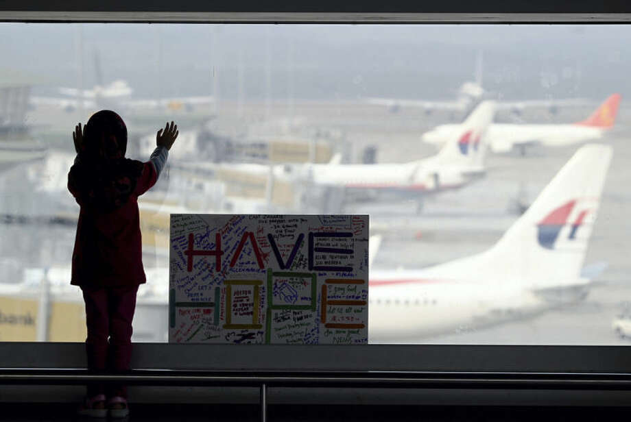 A girl stands next to a sign board made and written by the public at Kuala Lumpur International Airport in Sepang, Malaysia, Monday, March 10, 2014. Vietnamese aircraft spotted what they suspected was one of the doors of the missing Boeing 777 on Sunday, while questions emerged about how two passengers managed to board the ill-fated aircraft using stolen passports. (AP Photo/Daniel Chan)
