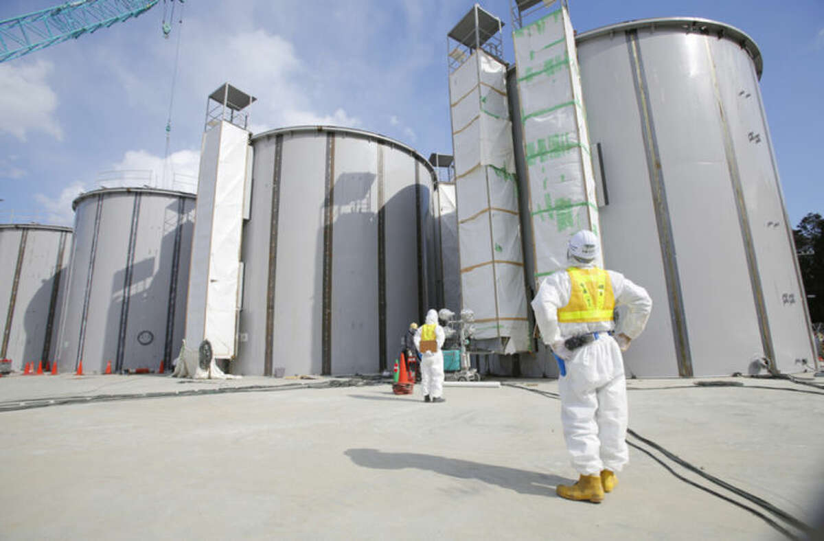 A worker in a protective suit and a mask looks at tanks, under construction, to store radioactive water, in the J1 area at the Tokyo Electric Power Co's (TEPCO) tsunami-crippled Fukushima Dai-ichi nuclear power plant in Okuma, Fukushima prefecture, northeastern Japan, Monday, March 10, 2014. (AP Photo/Toru Hanai, Pool)