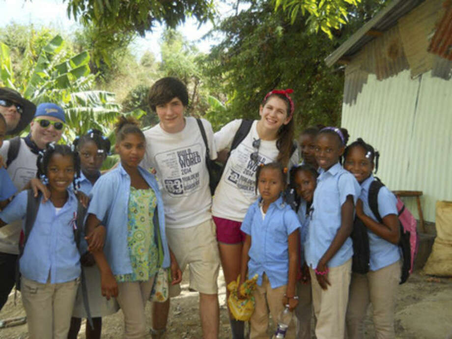 Contributed photoFour Staples High School students (l-r: Nick Moro-senior; Jimmy Ray Stagg- sophomore; Eli Debenham- freshman; Ale Benjamin-junior) take a break from work to spend time with children in the community of La Berma in the Dominican Republic.