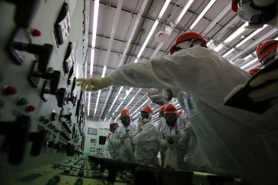 Members of the media and Tokyo Electric Power Co. (TEPCO) employees in protective suits and masks visit the central control room for the No. 1 and No. 2 reactors at the tsunami-crippled TEPCO's Fukushima Dai-ichi nuclear power plant in Okuma, Fukushima prefecture, northeastern Japan, Monday, March 10, 2014. (AP Photo/Toru Hanai, Pool)