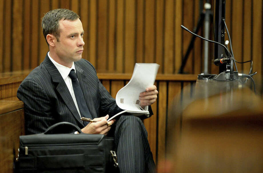 Oscar Pistorius sits in the dock as he listens to cross questioning in the second week of his trial about the events surrounding the shooting death of his girlfriend Reeva Steenkamp at court in Pretoria, South Africa, Monday, March 10, 2014. Pistorius is charged with the shooting death of his girlfriend Steenkamp, on Valentines Day in 2013. (AP Photo/Bongiwe Mchunu, Pool)